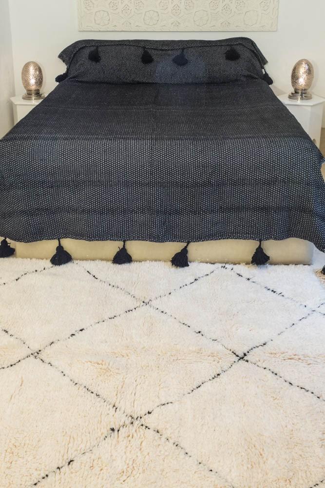 déco bohème fait main au maroc avec un tapis beni ouarain un plaid à pompons et des coussins à pompons en soie et coton
