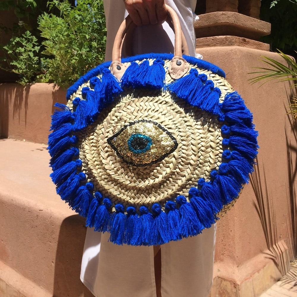 panier de plage pour l'été en feuilles de palmier et pompons et paillettes bleu fait à la main marque flo and jouls flo&jouls